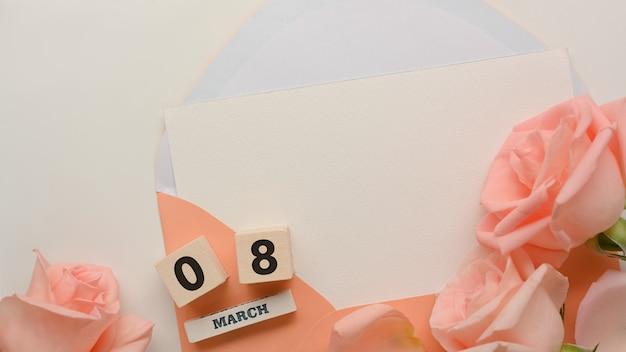 Mock-up kaart in pastel envelop in vrouwendag concept op witte tabelachtergrond met roze bloemen