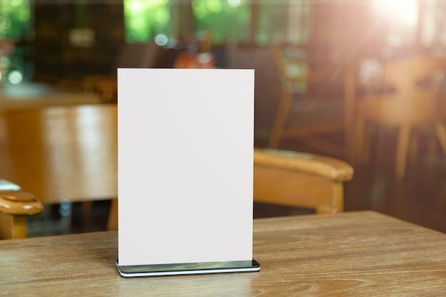 Mock-up label het lege menuframe in bar-restaurant. staan voor boekje met wit vel papier acryl tentkaart op tafel met wazige achtergrond kan de tekst of afbeelding invoegen
