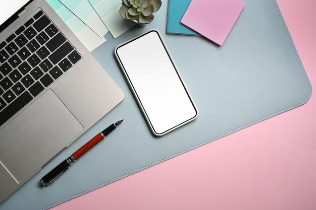 Mock-up laptop, smartphone, notebook en koffiekopje op roze achtergrond.