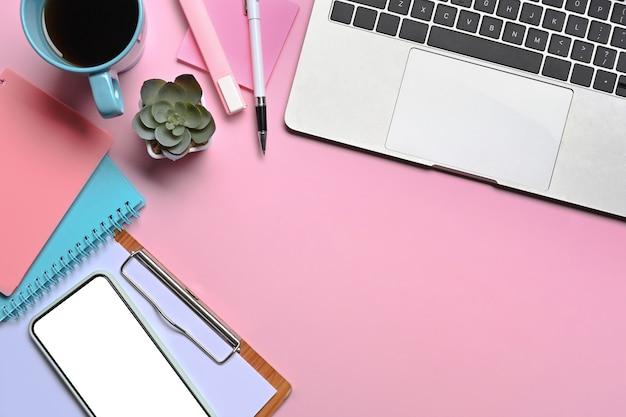 Mock-up laptop, smartphone, notebook, koffiekopje en papier werkt op roze achtergrond.