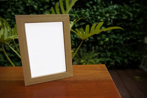 Mock up lege witte frame staande op houten tafel in bar restaurant cafe. ruimte voor tekst. product display montage.