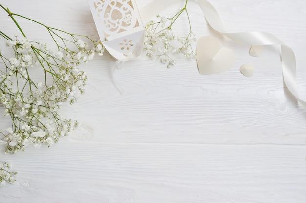 Mock up samenstelling van witte bloemen rustieke stijl, harten en een cadeau voor valentijnsdag met een plek