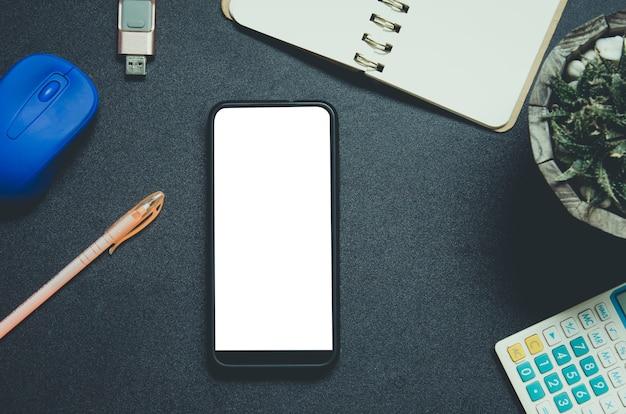 Mock up smartphone bovenaanzicht met muis, pen en rekenmachine op zwarte achtergrond