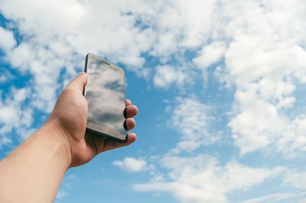 Mock up-smartphone op een blauwe hemel met wolken