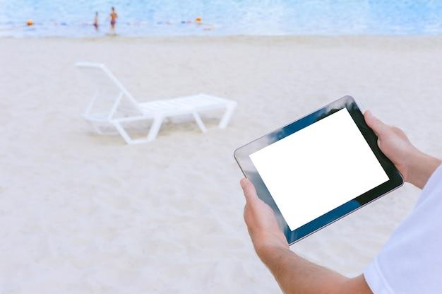 Mock-up tablet in de hand van een man. tegen de achtergrond van het strand en de ligstoelen. concept op het thema recreatie.