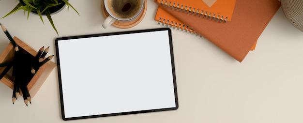 Mock-up tablet op witte werktafel met potloden, notebooks, koffiekopje en decoratie