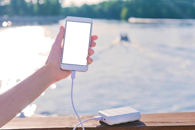 Mock-up telefoon in de hand van een meisje op de pier. laad je smartphone op met powerbank. tegen de achtergrond van de rivier, meer met een boot.