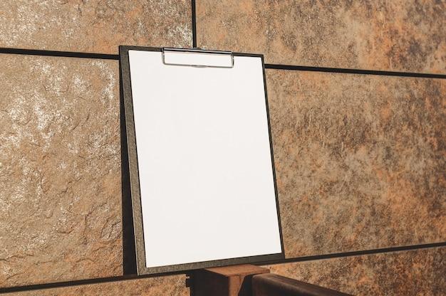 Mock up van de tablet voor het papier tegen de muur