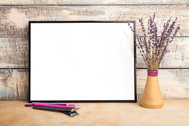 Mock up van een lege frame poster op een muur van houten planken. bosje lavendel in een vaas en kleurpotloden op tafel