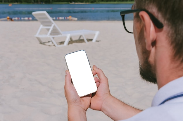 Mock up van een smartphone in de handen van een man op het strand. tegen de achtergrond van zand en water.