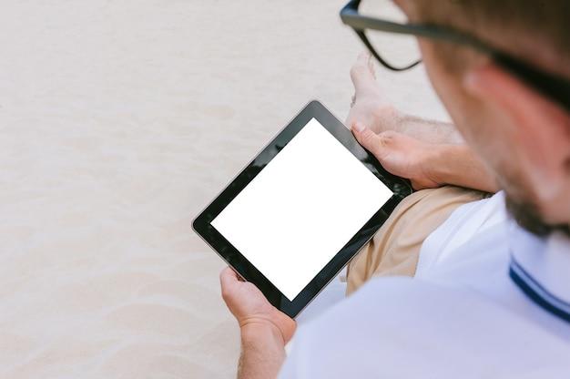 Mock-up van een tablet in de handen van een man die op een strand op een ligstoel ligt. tegen de achtergrond van zand.