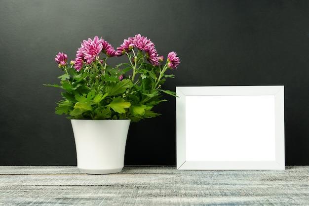 Mock up van een wit frame met een bloem in een witte pot op een houten tafel, zwarte muur. portret oriëntatie