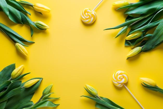 Mock up van gele tulpen met lolly op gele achtergrond, kopieer ruimte