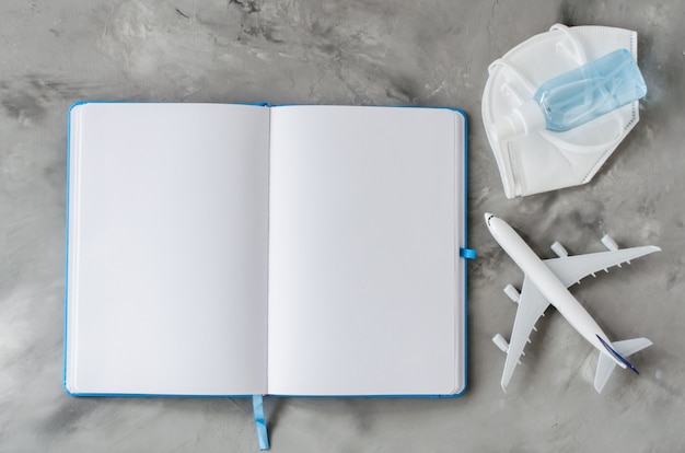 Mock up van notebook, vliegtuigmodel met gezichtsmasker en ontsmettingsmiddel