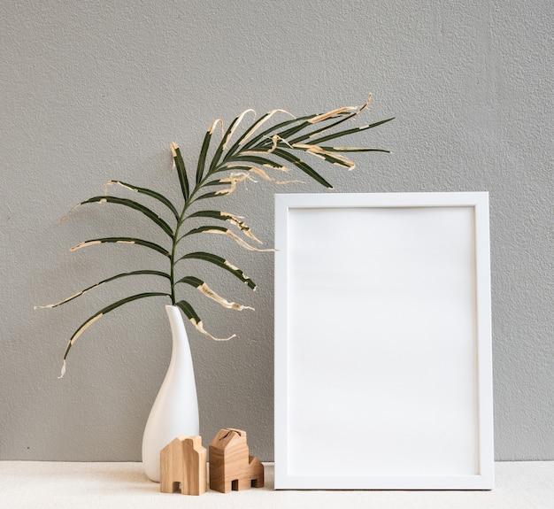 Mock-up van posterkaders met droge palmbladeren in witte keramische vaas en klein houten huismodel op beige bureau en groen muuroppervlak