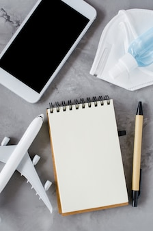 Mock up van smartphone met notebook, gezichtsmasker, gelfles en vliegtuigmodel