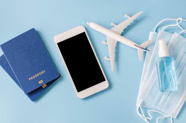 Mock up van smartphone met vliegtuigmodel, paspoorten, gezichtsmasker en handdesinfecterende spray