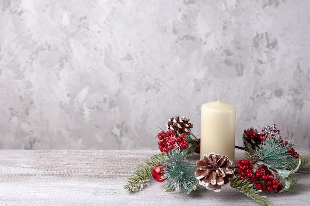 Mock-up van vanille dikke kerstkaars en krans van kerstboomtakken, kegels, rode bessen