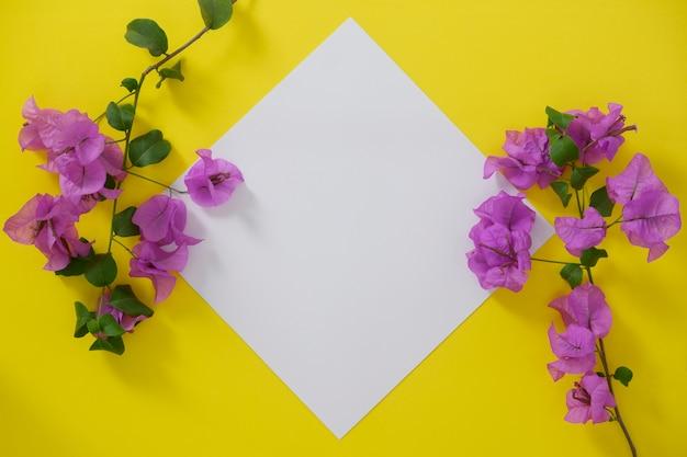 Mock-up witboek met ruimte voor tekst of afbeelding op gele achtergrond en bloemen.