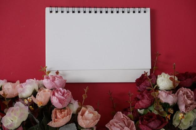 Mock-up witboek met ruimte voor tekst of afbeelding op rode achtergrond en bloem.