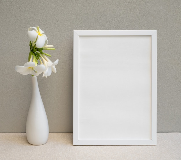 Mock up witte posterframe en prachtige plumeria of frangipani tropische bloemen in moderne witte vaas op beige tafel