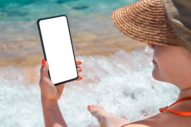 Mockup-afbeelding. hand houden en tonen modren mobiele mobiele slimme telefoon op het strand