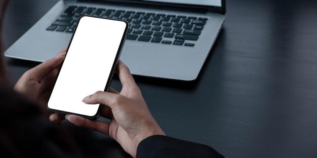 Mockup afbeelding leeg wit scherm mobiele phone.women hand met sms met behulp van mobiel op bureau op kantoor aan huis.