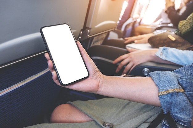 Mockup-afbeelding van de hand van de vrouw met een zwarte slimme telefoon met een leeg bureaublad in de cabine