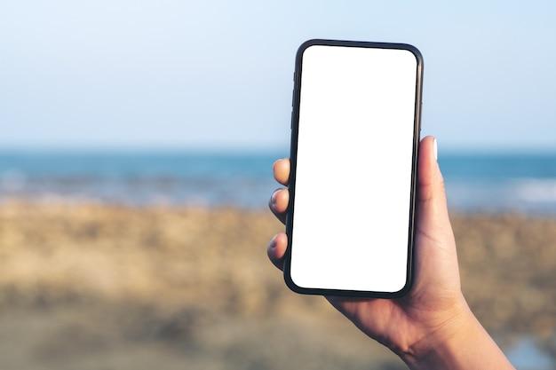 Mockup-afbeelding van de hand van de vrouw met zwarte mobiele telefoon met leeg bureaublad aan het strand en de zee met blauwe hemelachtergrond
