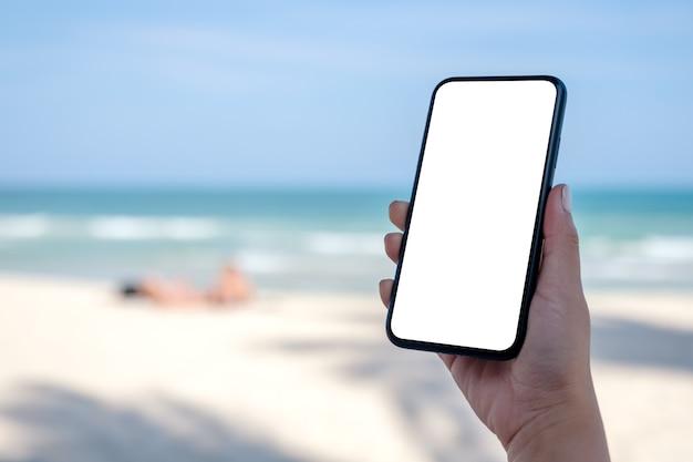 Mockup-afbeelding van de hand van de vrouw met zwarte mobiele telefoon met leeg bureaublad aan het strand en de zee