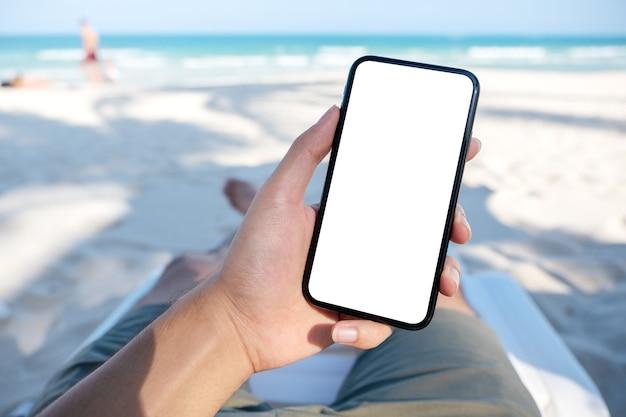 Mockup-afbeelding van de hand van een man die witte mobiele telefoon met een leeg bureaubladscherm houdt terwijl hij op de strandstoel ligt