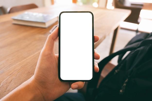 Mockup-afbeelding van de hand van een man die zwarte mobiele telefoon met leeg wit scherm vasthoudt en toont terwijl hij in café zit