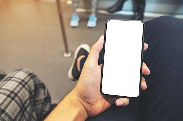 Mockup-afbeelding van de hand van een man met zwarte mobiele telefoon met leeg scherm in de metro