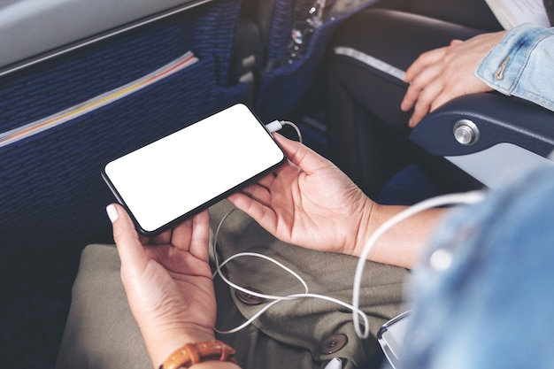 Mockup-afbeelding van de hand van een vrouw die een zwarte smartphone vasthoudt met een leeg desktopscherm en een oortelefoon in de cabine