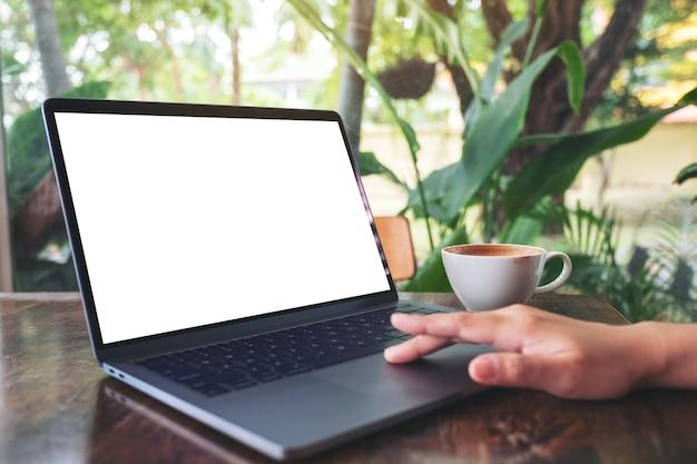 Mockup-afbeelding van de hand van een vrouw die op laptop touchpad gebruikt en aanraakt met een leeg wit desktopscherm met koffiekopje op houten tafel
