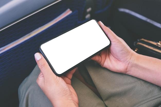 Mockup-afbeelding van de hand van een vrouw met een zwarte smartphone met een leeg desktopscherm in de cabine