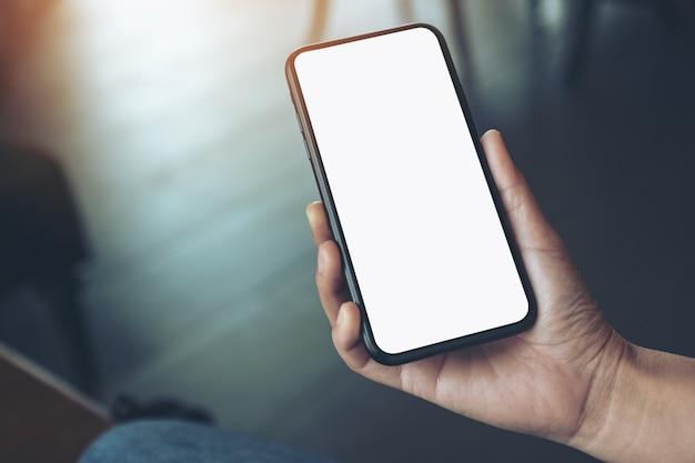 Mockup-afbeelding van de hand van een vrouw met zwarte mobiele telefoon met een leeg bureaublad