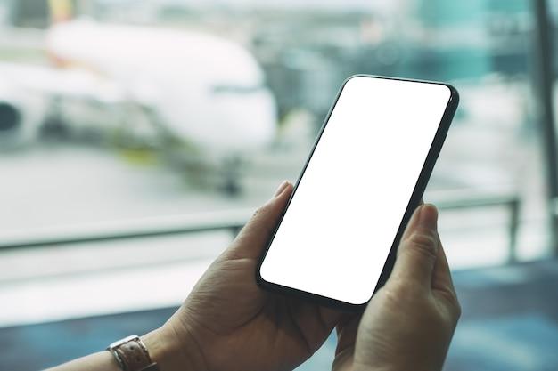 Mockup-afbeelding van de handen van een vrouw die een zwarte mobiele telefoon met een leeg scherm vasthoudt en gebruikt terwijl ze op de luchthaven zit