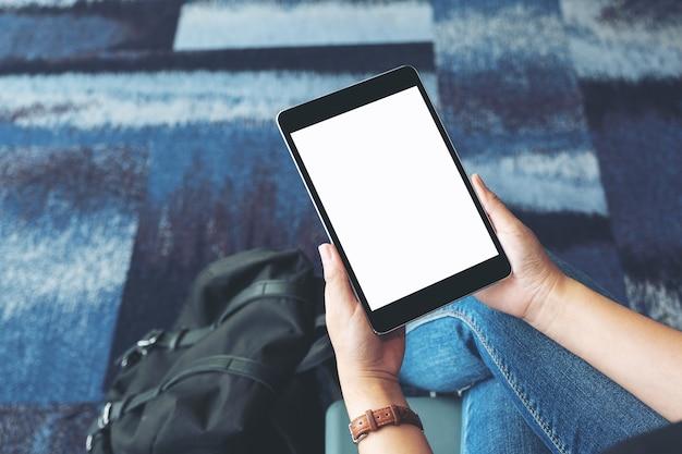 Mockup-afbeelding van de handen van een vrouw die een zwarte tablet-pc met een leeg wit scherm vasthoudt en gebruikt terwijl ze op de luchthaven zit