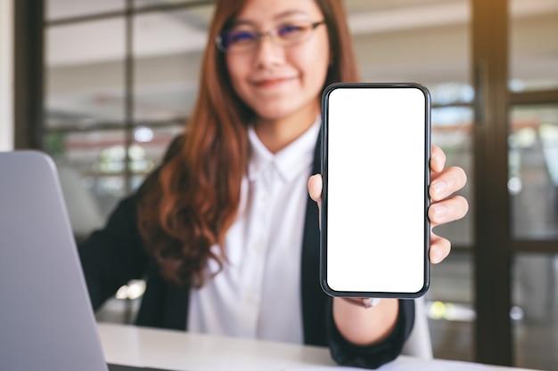 Mockup-afbeelding van een aziatische zakenvrouw die een zwarte mobiele telefoon vasthoudt en toont met een leeg wit scherm in café