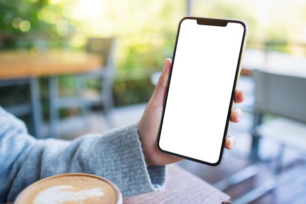 Mockup-afbeelding van een hand die een zwarte mobiele telefoon vasthoudt en toont met een leeg desktopscherm met een koffiekopje op tafel
