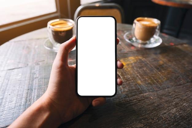 Mockup-afbeelding van een hand die een zwarte mobiele telefoon vasthoudt en toont met een leeg wit scherm en een koffiekopje op houten tafel