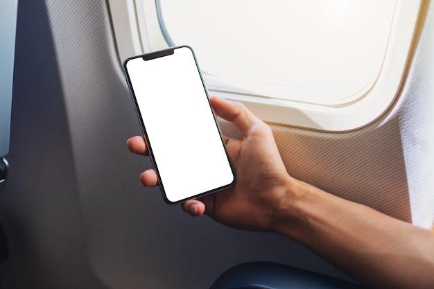 Mockup-afbeelding van een hand die een zwarte mobiele telefoon vasthoudt met een leeg desktopscherm naast een vliegtuigraam
