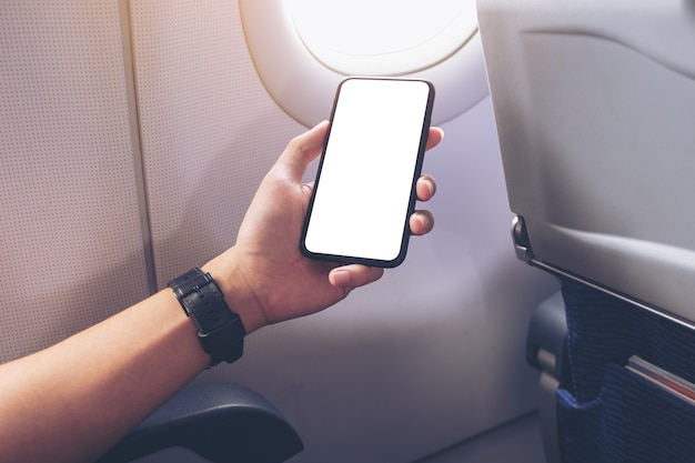 Mockup-afbeelding van een hand die een zwarte smartphone vasthoudt met een leeg desktopscherm naast een vliegtuigraam