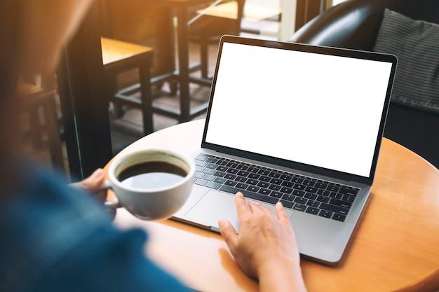 Mockup-afbeelding van een hand die het touchpad van een laptop gebruikt en aanraakt met een leeg wit bureaubladscherm terwijl je koffie drinkt