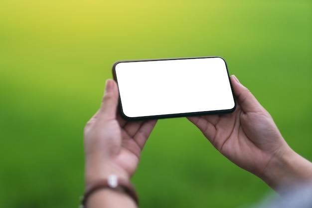 Mockup-afbeelding van een hand met zwarte mobiele telefoon met een leeg desktopscherm met onscherpe groene natuurachtergrond