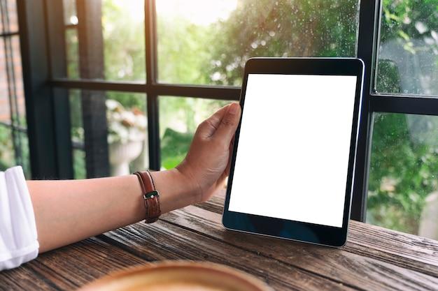 Mockup-afbeelding van een hand met zwarte tablet-pc met een leeg wit bureaubladscherm op houten tafel