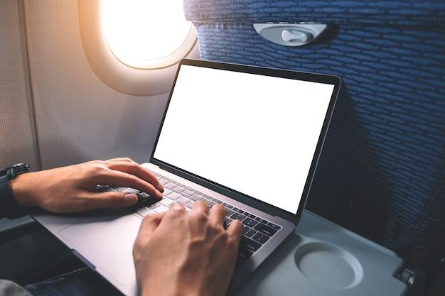 Mockup-afbeelding van een man die een laptop gebruikt en typt met een leeg wit bureaubladscherm terwijl hij in de cabine zit