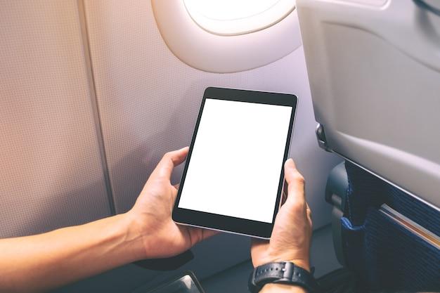 Mockup-afbeelding van een man die een zwarte tablet-pc vasthoudt en bekijkt met een leeg wit bureaubladscherm naast een vliegtuigraam