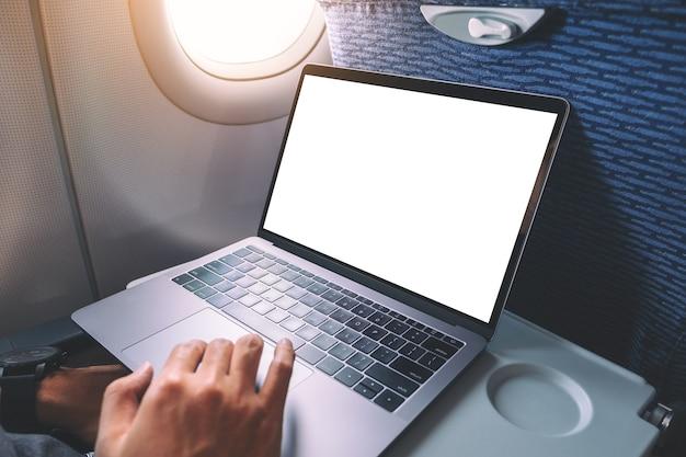 Mockup-afbeelding van een man die het touchpad van een laptopcomputer gebruikt en aanraakt met een leeg wit bureaubladscherm terwijl hij in de cabine zit